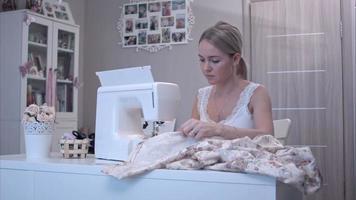 bela jovem usando máquina de costura elétrica