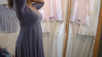mulher experimentando um vestido em um vestiário de boutique