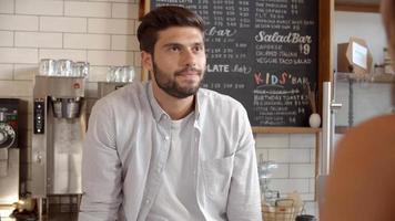 barista che prende il pagamento con carta da un cliente in una caffetteria video