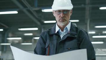 ingegnere senior in elmetto protettivo è in piedi in una fabbrica e sta guardando un progetto.
