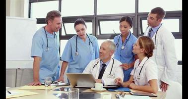 Ärzte schauen auf Laptop und diskutieren