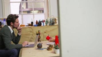 zwei 3d designer, die ein kreatives treffen in einem büro haben, erschossen auf r3d video