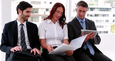 Geschäftsteam sitzt auf Stühlen und bespricht ihre Arbeit