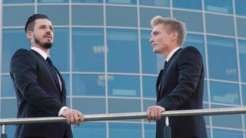 Retrato de dos hombres de negocios de pie en la terraza y discutiendo sus negocios