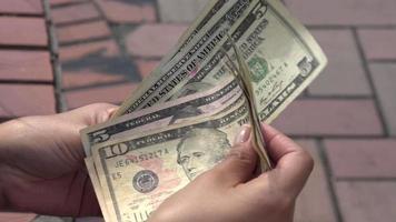 mujer sosteniendo billetes de un dólar