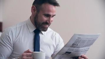 empresario disfrutando de periódico en la habitación del hotel video