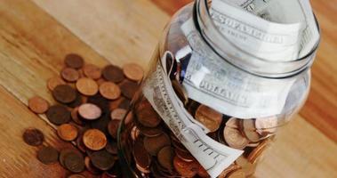 close-up de moedas e notas na garrafa