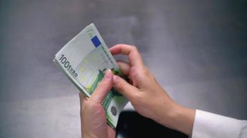 Ansicht einer Frau, die viele 100-Euro-Scheine zählt