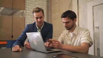 Dos hombres de negocios compran boletos en línea en juegos deportivos. video