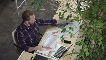 o barbudo se senta no escritório ambiental e olha as figuras no papel video
