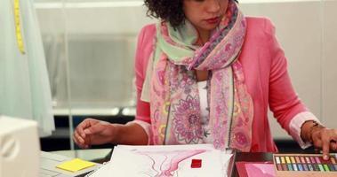 attraktive weibliche Modedesignerin, die bei der Arbeit zeichnet