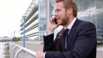 junger Geschäftsmann, der am Telefon durch Stadtfluss spricht video