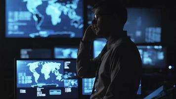 uomo con gli occhiali sta parlando al telefono in una stanza buia di monitoraggio piena di schermi.