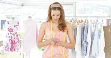 atractivo diseñador de moda enviando mensajes de texto por teléfono