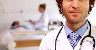 médecin souriant à la caméra dans la salle