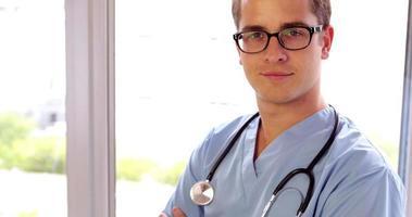 jeune chirurgien souriant à la caméra avec les bras croisés