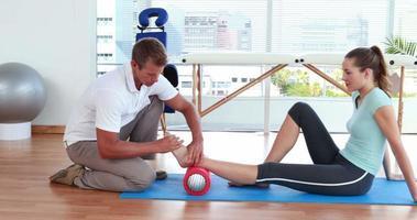 Physiotherapeut mit Schaumstoffrolle mit Patient