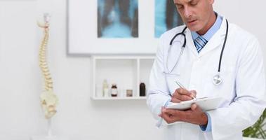 Arzt notiert etwas in seiner Zwischenablage