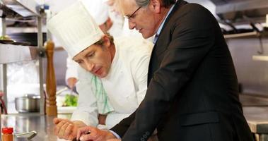 Man and chef looking at a clipboard