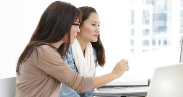 team creativo che lavora insieme sul laptop e guardando attraverso la cartella