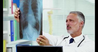 Porträt eines lächelnden Arztes, der eine Röntgenaufnahme hält