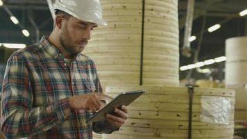 lavoratore sta utilizzando un tablet nel magazzino della fabbrica di legname.