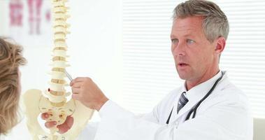 fisioterapista che spiega il modello della colonna vertebrale al paziente