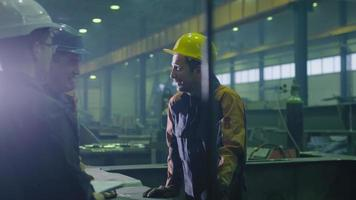 Group of heavy industry workers in hardhats are having a conversation in a factory. video
