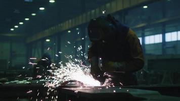 trabalhador da indústria pesada em uma fábrica está trabalhando com metal em uma esmerilhadeira enquanto faíscas quentes são produzidas em resultado disso.