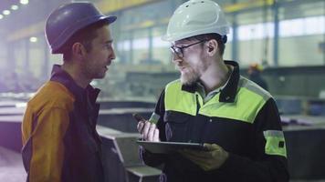 Un ingénieur et un ouvrier portant des casques ont une conversation dans une usine de l'industrie lourde. video