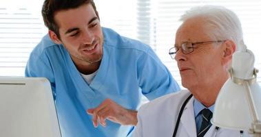 Doctor interactuando con su colega mientras trabaja en la computadora