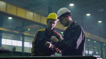 Manager und Ingenieur in Schutzhelmen unterhalten sich in einer Schwerindustriefabrik.