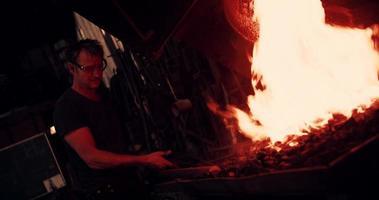 fabbro che lavora il ferro su una fucina con il fuoco al rallentatore