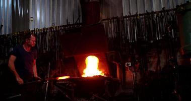 ferreiro trabalhando ferro em uma forja com fogo em câmera lenta