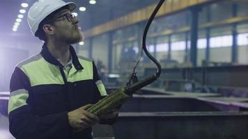 Schwerindustrie-Arbeiter in einer Fabrik halten eine Fernbedienung, die einen Kran bedient.