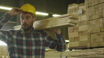 Lumber mill worker in hardhat is carrying wood in warehouse.