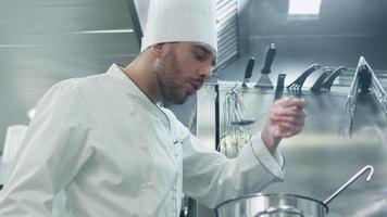 feliz chef profissional em uma cozinha comercial de um restaurante ou hotel está degustando sopa.