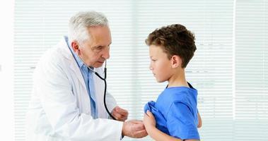 männlicher Arzt, der einen Jungen untersucht video