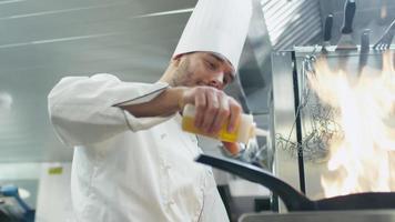 chef profesional en una cocina comercial está preparando comida con fuego en una sartén.