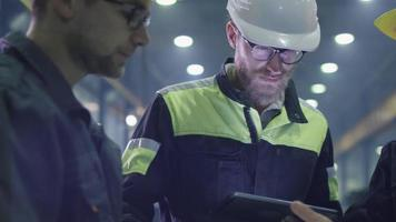 Team of workers at a heavy industry factory have a conversation while looking at a blueprint. video