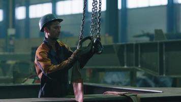 tung industriarbetare på en fabrik driver en kran med fjärrkontroll.