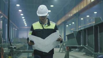 ingénieur en casque se déplace dans une usine de l'industrie lourde avec un plan. video