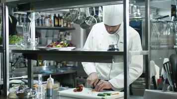chef professionista in una cucina commerciale sta affettando verdure verdi.