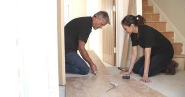 El hombre y la mujer sentar suelos de paneles de madera laminada en una casa