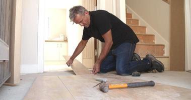 uomo posa pavimenti in pannelli di legno laminato in una casa