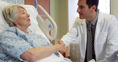 il medico parla al paziente anziano nel letto di ospedale girato su r3d