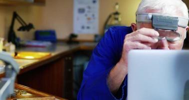 orologiaio utilizzando laptop durante la riparazione di un orologio