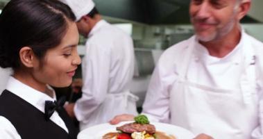 lächelnde Kellnerin wird vom Küchenchef ein Gericht gereicht