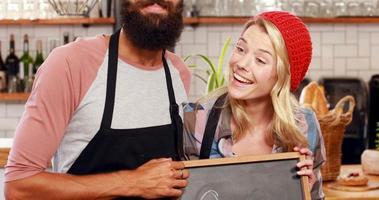 pareja hipster con cartel abierto