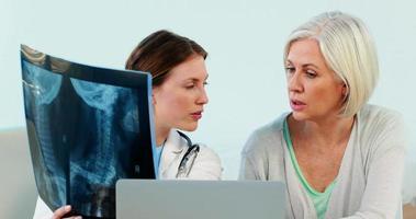 Ärztin, die über einen Röntgenbericht mit einer Patientin interagiert